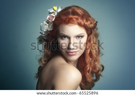 Young beautiful red haired woman smiling with an orchid in her hair, bright blue background - stock photo