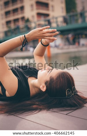 Young beautiful reddish brown hair caucasian girl lying down on a sidewalk using a smart phone - technology, social network, communication concept - stock photo