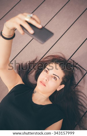 Young beautiful reddish brown hair caucasian girl lying on a sidewalk using a smartphone taking selfie - technology, social network, communication concept - dressed with blue jeans and black shirt - stock photo