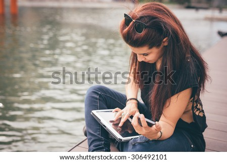Young beautiful reddish brown hair caucasian girl seated on a sidewalk using a tablet looking the screen - technology, social network, communication concept - dress with black shirt and blue jeans - stock photo
