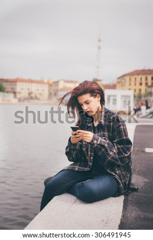 Young beautiful reddish brown hair caucasian girl using a smartphone seated on a sidewalk on Navigli, looking down the screen - technology, social network, communication concept - stock photo