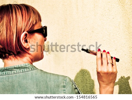 Young beautiful redhead using electronic cigarette - stock photo