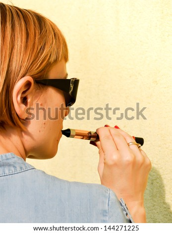 Young beautiful redhead using electronic cigarette, safer imitation of normal cigarette - stock photo