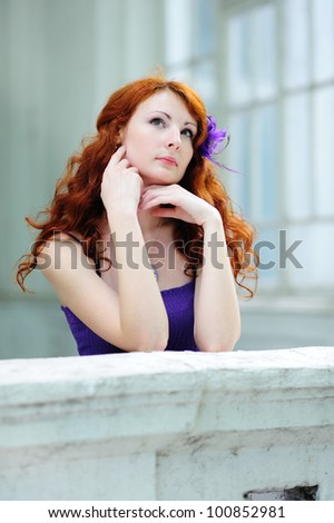 Young beautiful redhead woman portrait standing on balcony.