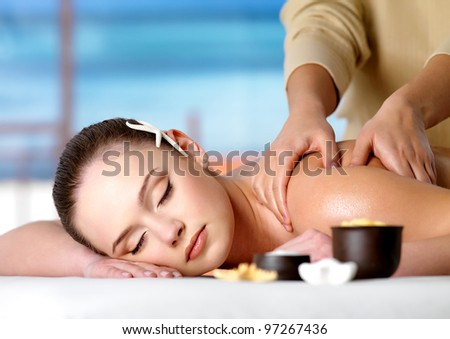 Young beautiful relaxing woman getting spa massage of shoulder in beauty salon - stock photo