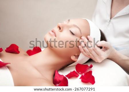 Young beautiful relaxing woman having a facial massage - stock photo