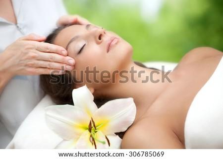 Young beautiful relaxing woman having a facial massage. - stock photo