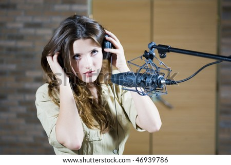 Young beautiful retro woman recording the sound in professional studio with mic and phones. indoor - stock photo