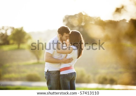 Young beautiful romantic couple in backlit composition - stock photo