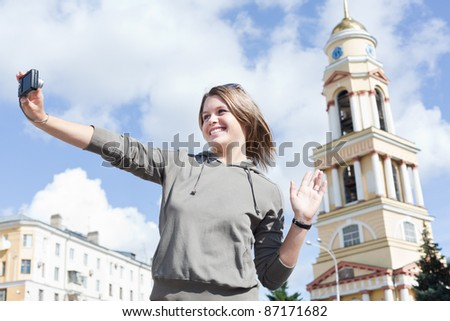 Young beautiful Russian woman photographing of himself against the the city's attractions, outdoors. Russia - stock photo