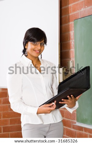 young beautiful school teacher standing in front of blackboard - stock photo