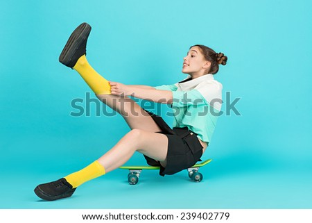 Young beautiful sensual crazy girl posing on a blue background with a Longboard wearing a fashionable outfit, smiling pulls the yellow leggings - stock photo