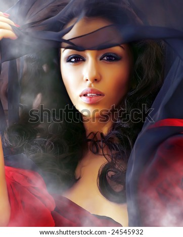 Young beautiful sexual woman in smoke clubs slightly opens a veil, showing the well-groomed person - stock photo
