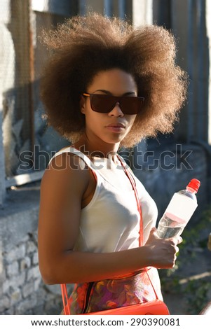 Young beautiful, sexy black girl posing and flirting in the summer park near the old building - stock photo