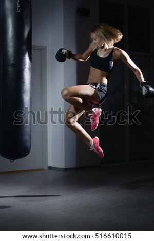 Young beautiful sexy boxer woman making kick