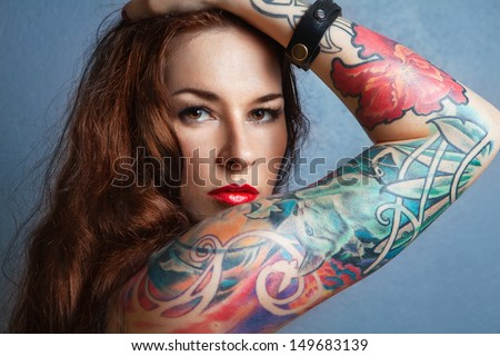 Young beautiful sexy brunette with gorgeous tattoo on her arms. tattoo - stock photo