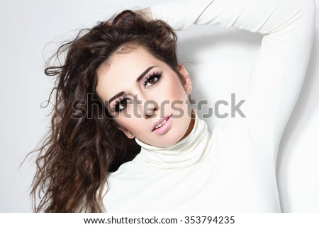 Young beautiful sexy brunette with long curly hair and false eyelashes - stock photo