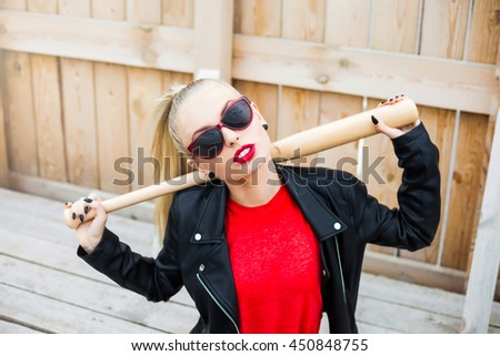 Young beautiful sexy cheeky hipster girl, tomboy, blonde with a baseball bat near the wooden wall, perfect makeup and stylish hairstyle, red lips, sunglasses, summer style. Fashion Beauty Swag. - stock photo