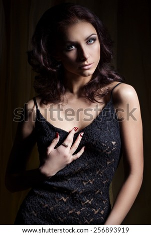 young beautiful sexy girl with a gentle makeup and beautiful hair in a black lace dress with dark lighting in the Studio - stock photo
