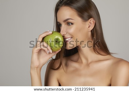 Young beautiful sexy girl with dark hair, bare shoulders and neck, holding big green apple to enjoy the taste and are dieting, healthy eating and organic foods, feeling temptation, smile, teeth - stock photo