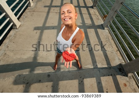 Young beautiful sexy smiling woman in white tank top in sunset light on a pier, holding watermelon heart