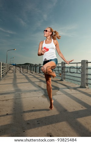 Young beautiful sexy smiling woman running in sunset light on a pier, holding watermelon heart - stock photo