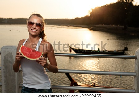 Young beautiful sexy smiling woman with windy hairs in sunset light on a pier, holding watermelon - stock photo