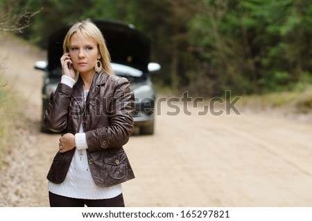 Young beautiful sexy woman at broken car with mobile phone, standing in the public road in forest area, calling for help with mobile phone. Broken vehicle in the background.  - stock photo