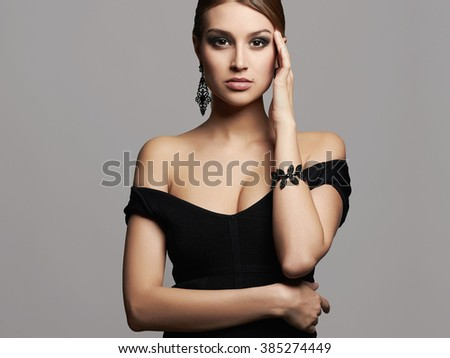 young beautiful sexy woman.Beauty girl with short hair and make-up.elegant lady in black dress and jewelry - stock photo