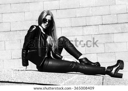 Young beautiful sexy woman in black skin clothes happy outdoors black and white  - stock photo