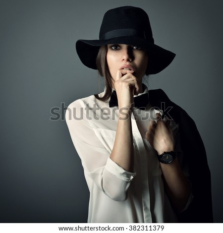 Young beautiful sexy woman in jacket, white shirt, bow-tie and hat over gray background. Fashion female portrait. Tomboy. - stock photo