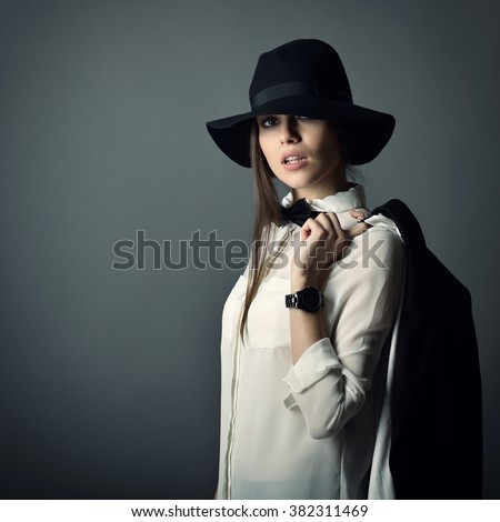 Young beautiful sexy woman in jacket, white shirt, bow-tie and hat over gray background. Fashion female portrait. Tomboy. Girl gets on men's clothes. - stock photo