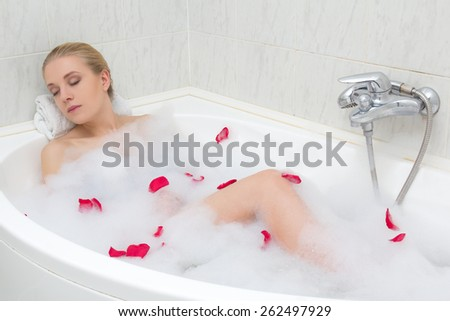 young beautiful sexy woman relaxing in bath with red flower petals - stock photo