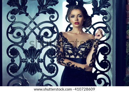 Young beautiful sexy woman wearing black lace evening dress with decollete, makeup with red lips and hairstyling standing at background of cast iron tracery lattice. Fashion vogue style portrait.