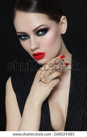 Young beautiful sexy woman with stylish make-up and vintage glasses in her hand - stock photo