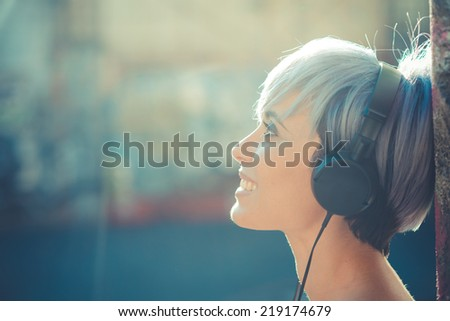 young beautiful short blue hair hipster woman with headphones music in the city - stock photo