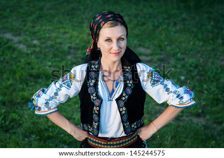 Young beautiful singer posing in traditional costume, romanian folklore - stock photo