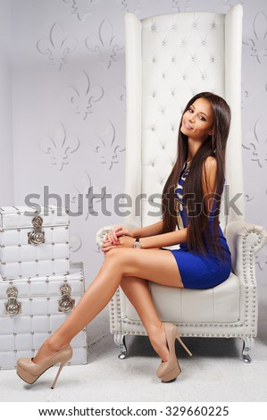 Young, beautiful, slender, swarthy, brunette girl with model looks in a little black dress with long, straight, beautiful, healthy, shiny hair, brown eyes and charming snow-white smile in the interior - stock photo