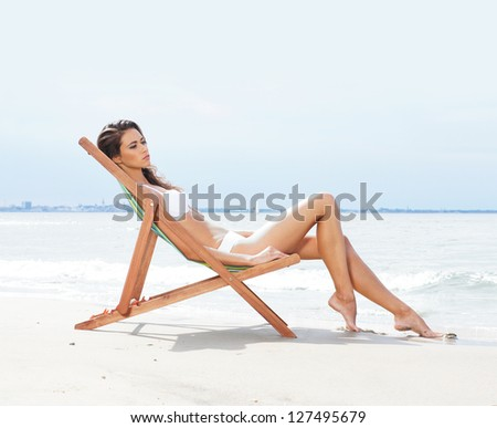 Young, beautiful, slim and sexy woman on the beach - stock photo