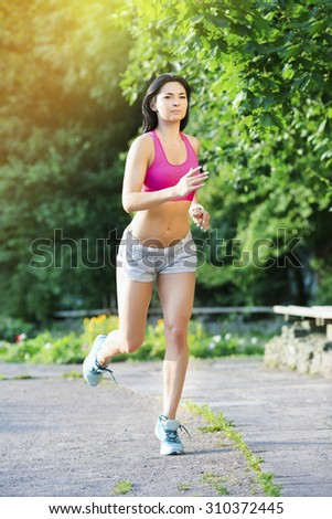 Young beautiful slim girl, wearing in pink top and gray shorts, jogging in the green park in summer day, full body - stock photo