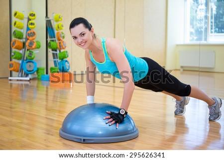 young beautiful slim woman doing push ups with bosu ball in gym - stock photo