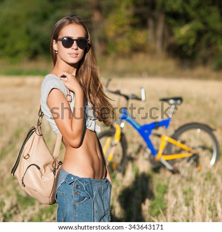 Young beautiful slim woman outdoors portrait with bike - stock photo