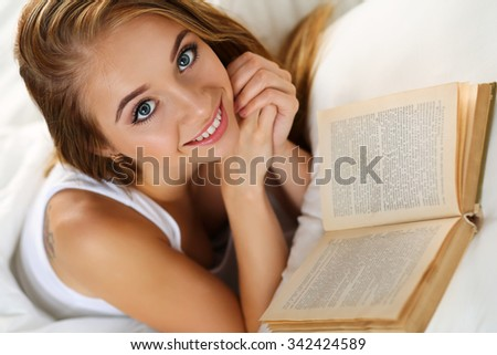 Young beautiful smiling blonde woman lying in bed reading book before or after sleeping. Hobby, favourite literature, reading for examination, education, work in bed, reference book concept - stock photo