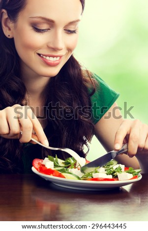 Young beautiful smiling brunette woman eating salad, outdoor - stock photo