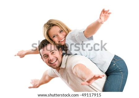Young beautiful smiling couple having fun together with piggyback and arms outstretched isolated on white background - stock photo
