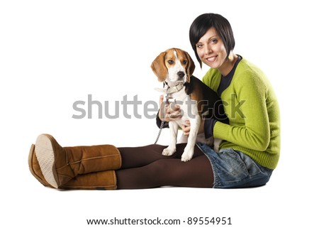 Young beautiful smiling girl holding her young dog (Beagle) in lap and posing.Isolation on white
