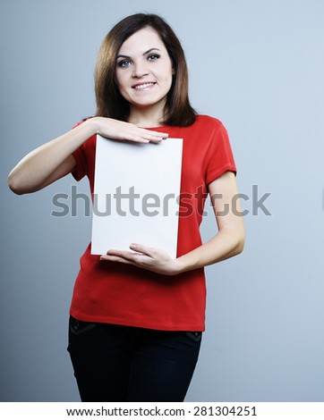 Young beautiful smiling girl in a red shirt with poster in hands on a gray background