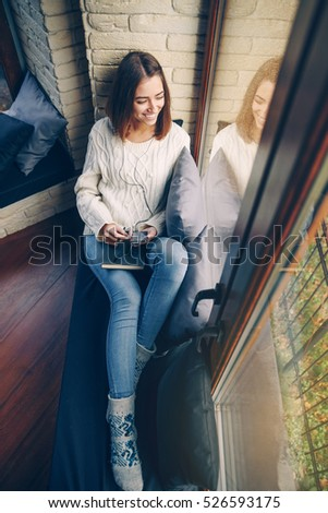 Young beautiful smiling girl in a white sweater and jeans sitting on the window sill holding a smart phone and sketchbook in hands and listening to music