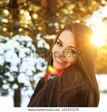 young beautiful smiling girl portrait in winter forest - stock photo