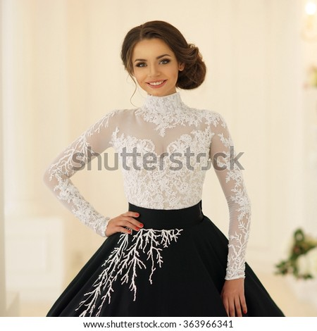 Young beautiful smiling girl posing in white interior in white and black evening dress with fluffy skirt - stock photo